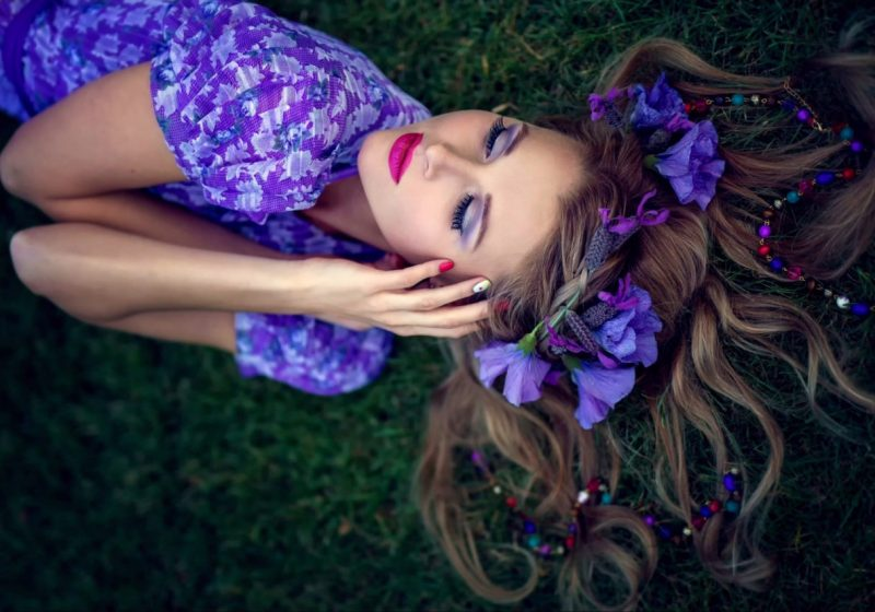 Practice Woman's Sahasrara Chakra Healing beautiful woman in violet laying on the earth with purple flowers   The Sublime Woman