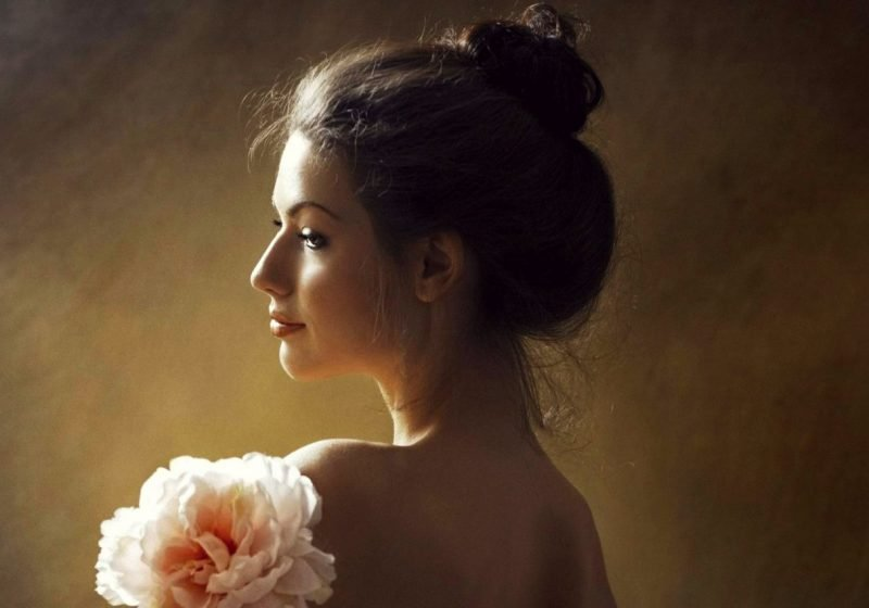 Feminine Stress Relief Stress and Femininity beautiful young woman smiling with a flower | The Sublime Woman